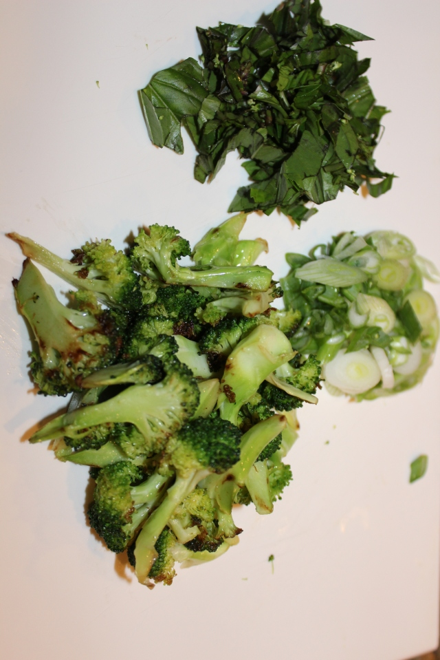 Toppings for soup: broccoli florets, ribbons of basil and sliced scallions