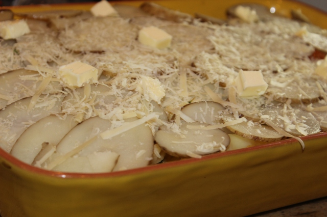 Top with sliced, partly boiled potatoes. Dot with butter and sprinkle your favorite melting cheese.
