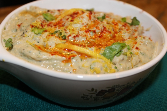 Baba ganoush is a creamy, tangy dip made with sesame seed paste (tahini) and mashed roasted eggplant, garnished with generous drizzles of olive oil and paprika.